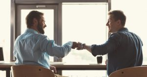 Two Employees Fist Bumping Showing Favouritism