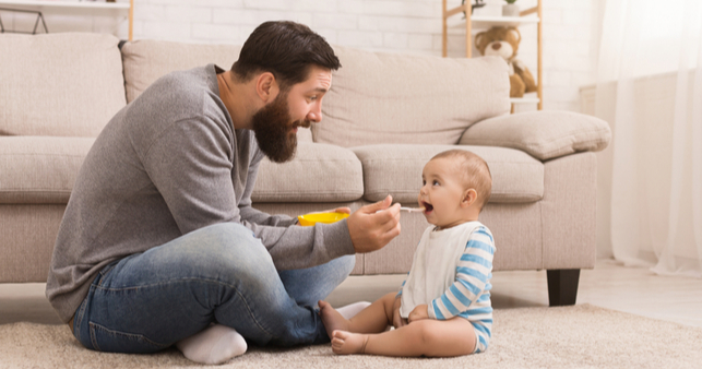 father on parental leave feeding his child